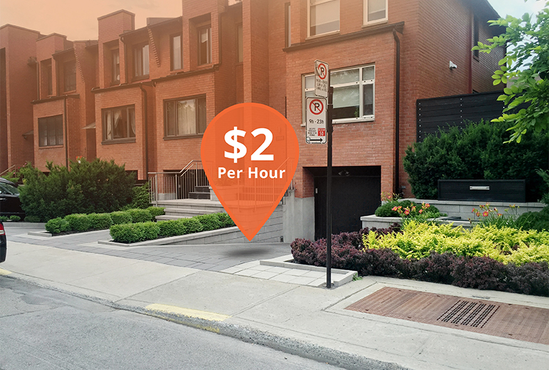 A townhouse with an empty driveway that features a pic that reads '$2 per Hour'.